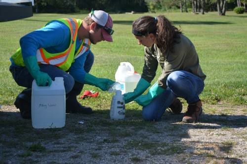 Two members of our staff prepare herbicide.